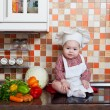 Baby cook with vegetables sits on a kitchen table — Stock Photo #19934827