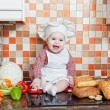 Baby cook with bread and steering-wheels sits on a kitchen table — Foto de Stock