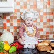 Baby cook with bread and steering-wheels sits on a kitchen table — Photo