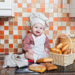 图库照片: Baby cook with bread and steering-wheels sits on a kitchen table