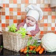 Child sits in a wattled basket on a table with vegetables — Stock Photo