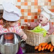 Two sisters play cooks in kitchen — Stock Photo