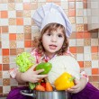 Baby cook with vegetables sits on a kitchen table — Stock Photo
