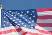 Flag of the USA against the blue sky — Stock Photo