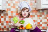 Baby cook with vegetables sits on a kitchen table — Zdjęcie stockowe