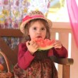 Stock video: Little girl eats big piece of water-melon with appetite