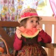 Stock Video: Little girl eats a big piece of a water-melon with appetite