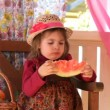 Vídeo Stock: Little girl eats big piece of water-melon with appetite