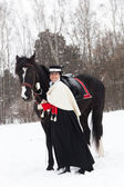 Girl keeps the Oryol trotter in black riding habit — Stock Photo