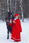 Woman in red riding habit sits astride the Oryol trotter — Stock Photo