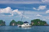 White catamaran to stand against rocks. Thailand — Stock Photo