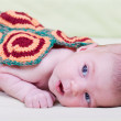 Newborn baby lies, covered with a knitted blanket — Stock Photo #23094724
