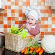 Royalty-Free Stock Photo: Child sits in a wattled basket on a table with vegetables