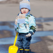 Little boy with a toy yellow shovel costs in a pool — Stock Photo #23981195