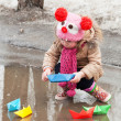 Little girl plays with paper ships in a spring puddle — Stock Photo