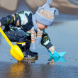 Little boy plays with paper ships in a spring puddle — Stock Photo