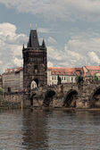 Prague, view of Karlov Bridge and tourists going on it — Stock Photo