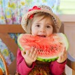 图库照片: Little girl in straw hat with appetite eats ripe water-melon
