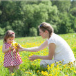 Mother with the small daughter play on a glade with dandelions — Stock Photo