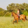 Stock Photo: Beautiful girl riding horse in countryside