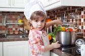 Holčička hraje kuchař a dělá na večeři — Stock fotografie