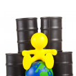 Toy  little man sits next on butts to oil the globe. The world supremacy concept oil-extracting the companies — Stock Photo