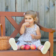 Little girl in a summer dress sits on a wooden shop with apples — Stock Photo