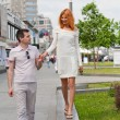 Stock Photo: Young loving couple walks in the summer around the city