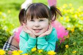 Portret van het meisje liggend op een glade met paardebloemen — Stockfoto