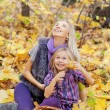Happy mum and the daughter play autumn park on the fallen down foliage — Stock Photo #27208525