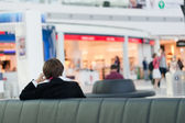 Business woman in a waiting room at the airport — Stok fotoğraf