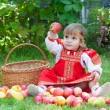 Little girl in the Russian national dress with a basket of apples — Stock Photo