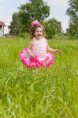 Cheerful girl in a pink dress runs on a grass — Stock Photo
