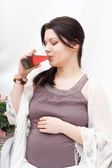 Young pregnant woman drinks juice — Stock Photo