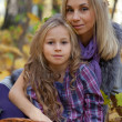 Happy mum and the daughter play autumn park on the fallen down foliage — Stock Photo #28192465