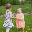 Two little girls with dandelions — Stock Photo