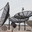 It is a lot of television satellite antennas on a house roof against the sky — Stock Photo #28192643