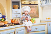 Little boy sits on a kitchen table and plays the cook — Stock Photo
