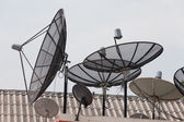 It is a lot of television satellite antennas on a house roof against the sky — Stock Photo
