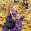 Stock Photo: Happy mum and daughter play autumn park on fallen down foliage