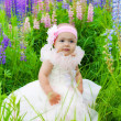 Little girl in an elegant dress sits on a grass — Stock Photo