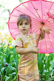 Little girl in a kimono with a pink umbrella — Stock Photo