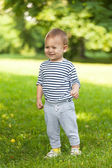 Little boy walks in the summer on a solar clearing — Stock Photo