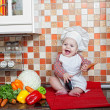 Baby cook with vegetables sits on a kitchen table — Stock fotografie