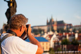 Mature male photographer photographs morning Prague — Stock Photo