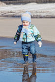 Little boy goes on a pool in rubber boots — Stock Photo