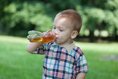Little boy drinks juice on the street — Stock Photo