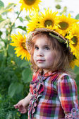 Little girl in a summer hat among sunflowers — Stock Photo