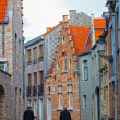Two persons go on the old street to Bruges, the wall has a bicycle — Stock Photo #33228295