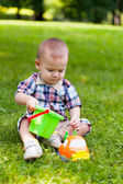 Little boy sits on a grass and plays toys — Stock Photo